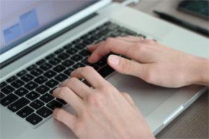 Schreiben auf der Tastatur eines Laptop in CAS genesisWorld CRM