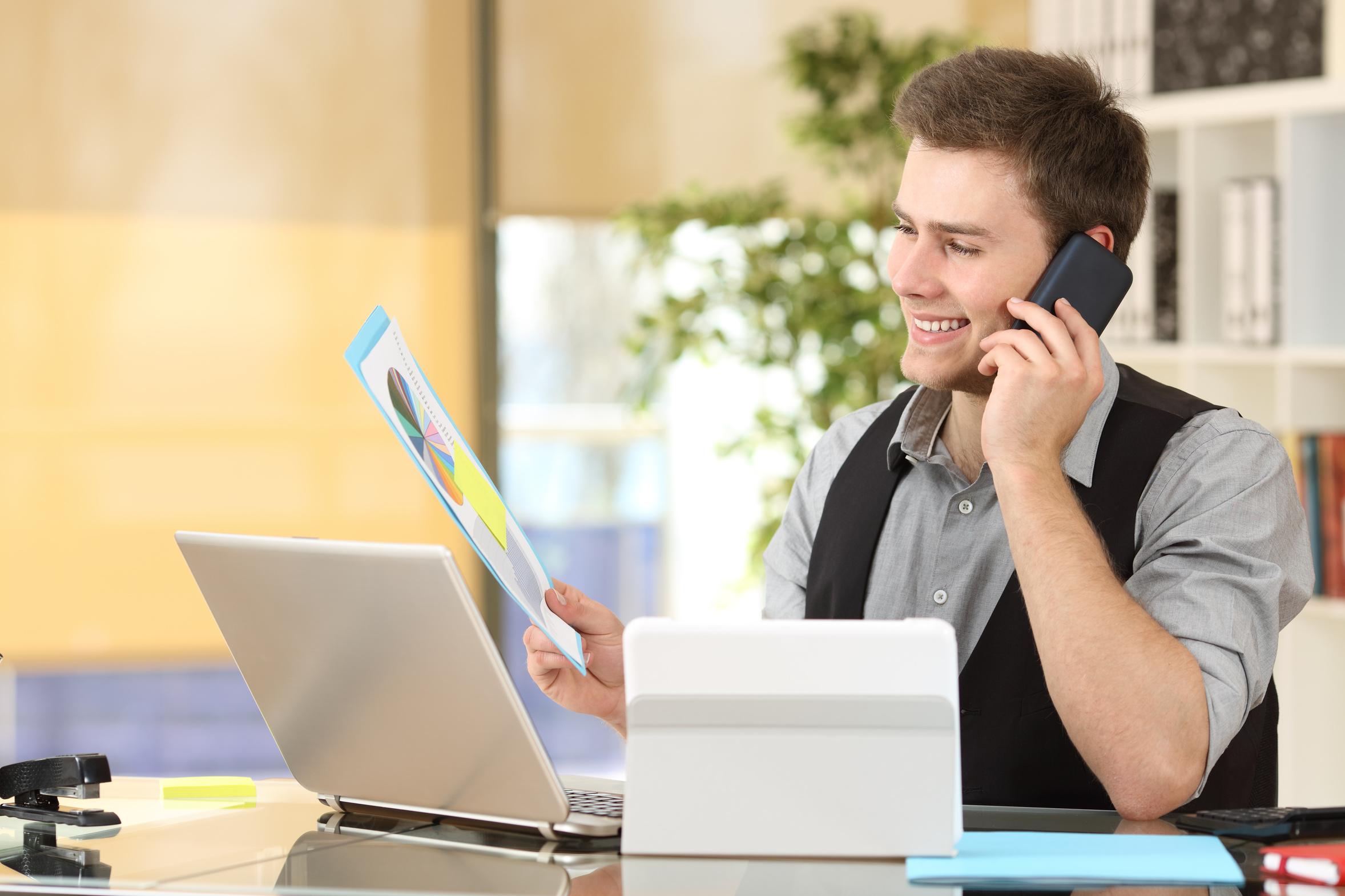 Telefonierender freundlicher Mann mit Unterlagen am Computer und Tablet