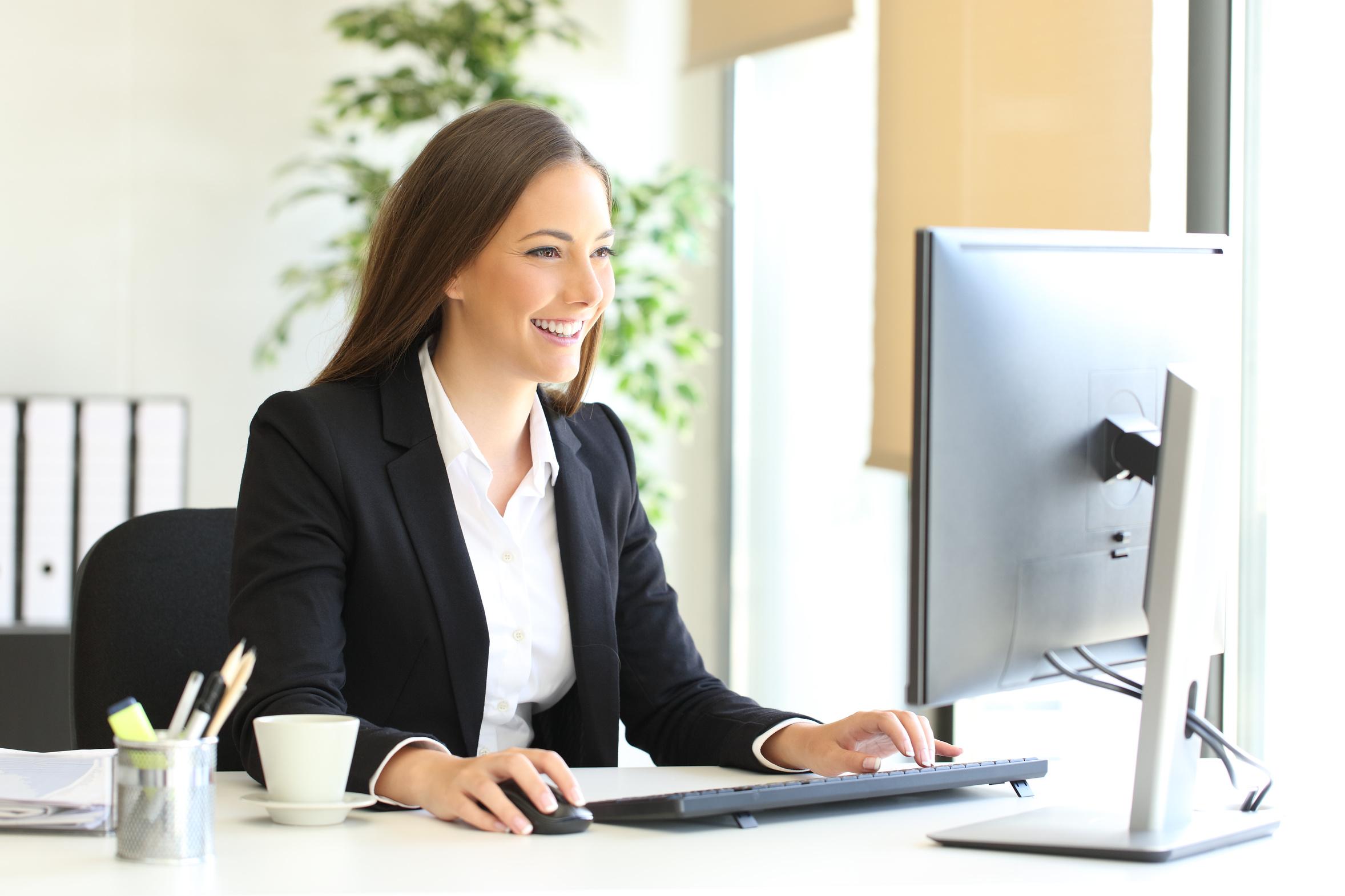 Lächelnde Frau am Computer arbeitend nach rechts sehend
