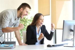 Glückliche Mitarbeiter erhalten News über den Computer