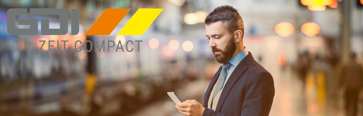 Mann am Bahnhof nutzt GDI Zeit auf dem Smartphone