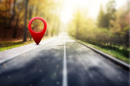 Roter GPS-Marker auf einer Herbststraße