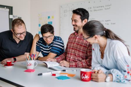Glückliche Mitarbeiter erarbeiten im Team ein neues Projekt