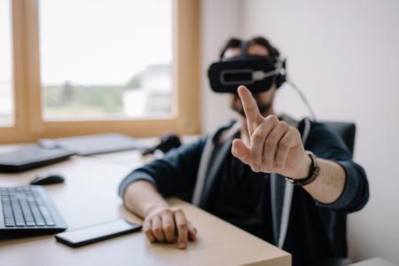 Mitarbeiter am Schreibtisch mit Virtual Reality Brille nimmt am Meeting mit einem virtuellen Team teil