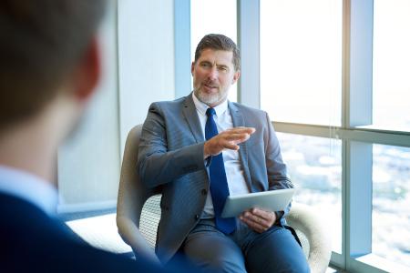 Ein Anwalt berät einen Kunden mithilfe der Kanzlei CRM Software