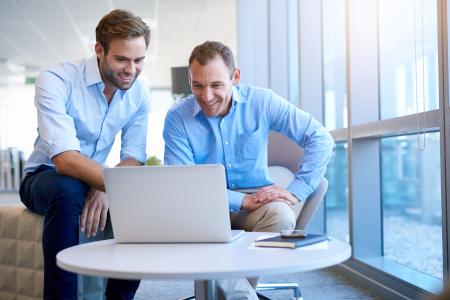 Mitarbeiter teilen gute Nachrichten am Laptop in einem modernen Büro.